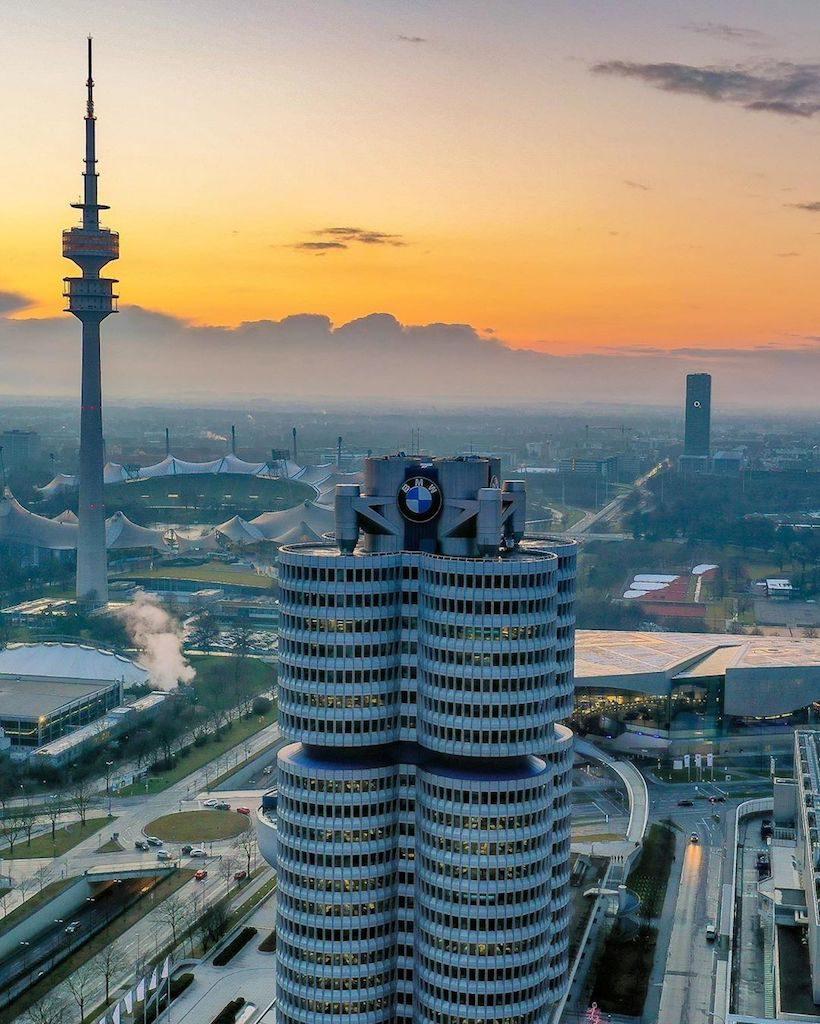 Dronenaufnahme eines Sonnenuntergangs in München mit Blick auf den Hauptsitz von BMW, dem Fernsehturm und dem Olympiapark im Hintergrund
